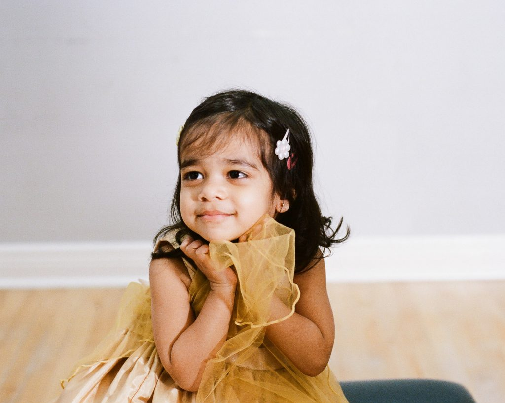 toddler girl shyly posing for studio portraits wearing golden yellow dress